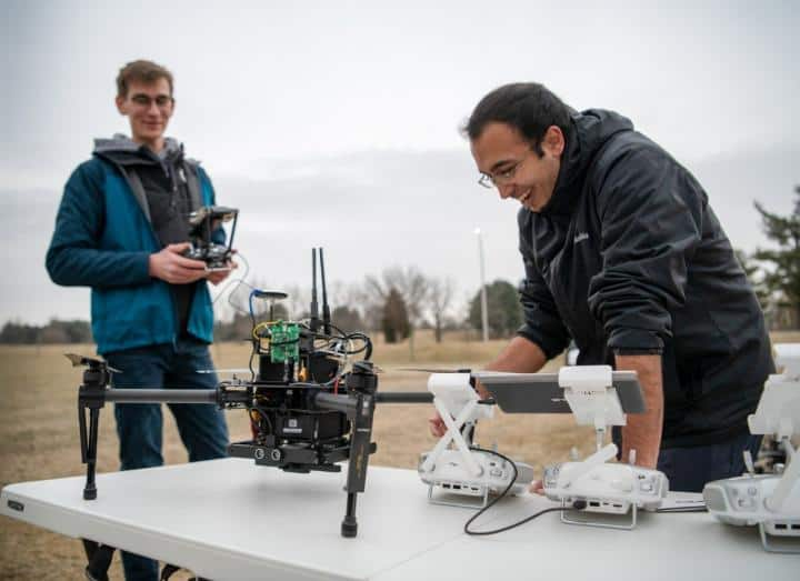 Larkin Heintzman (left) and Pratik Mukherjee, both doctoral students in the Department of Electrical and Computer Engineering, calibrate several drones before flying them at Virginia Tech's drone park. These students are working alongside research faculty to effectively integrate drones and artificial intelligence into lost person search and rescue processes.